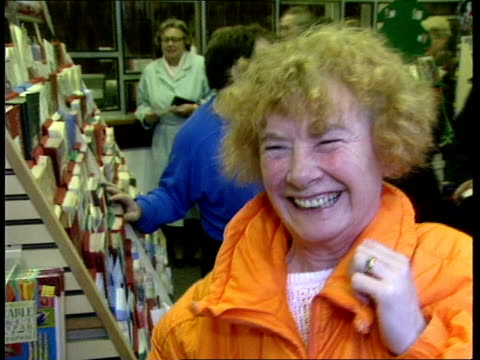 first draw; itn england: hertfordshire: hemel hempstead cms side woman taking money from customers and putting lottery numbers into computer bv queue... - lotterie stock-videos und b-roll-filmmaterial