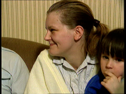 national lottery winners; national lottery winners; 22.30 scotland: glasgow cms ian judge sitting using phone with young son beside cms his wife with... - vox populi stock-videos und b-roll-filmmaterial