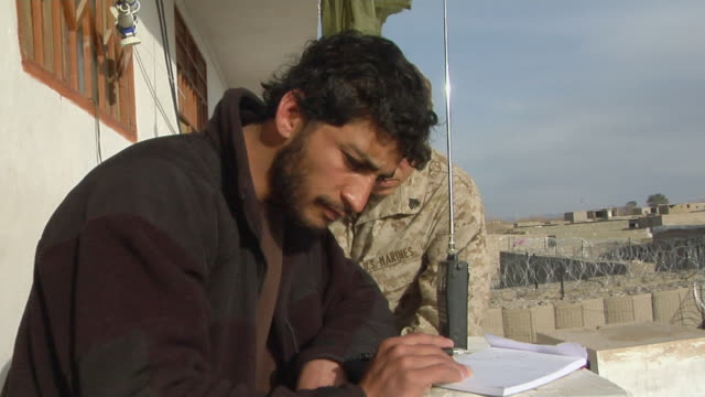 stockvideo's en b-roll-footage met national police listening radio and explaining to soldier / musa qala helmand province afghanistan - vertaling
