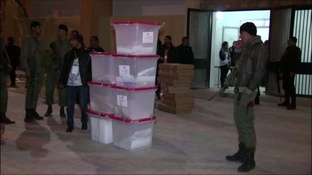 national security forces stand guard next to ballot boxes outside and inside of the indoor sports hall in kasserine province of tunisia before the... - 2014 stock videos and b-roll footage
