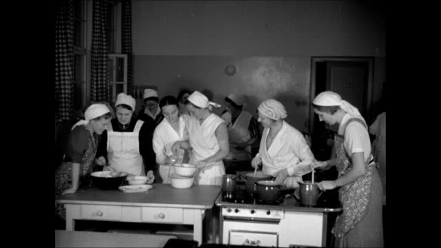 national socialist women's league, nazi women in coking class kitchen. cult of motherhood campaign: nurse demonstrating w/ doll how to pick up &... - nazism stock videos & royalty-free footage