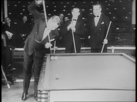 national three cushion billiard tournament / allan hall steeply angles cue and makes mass shot / crowd and pool players in tuxedos look on / joe... - pool cue sport stock videos & royalty-free footage