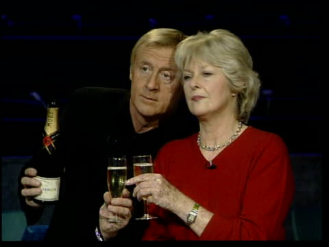National TV awards LIB Presenter Chris Tarrant posing with Judith Keppel as both hold glasses of champagne