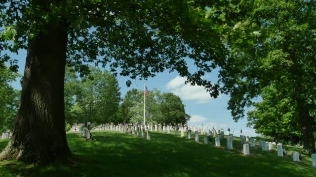 national veterans cemetery under oak tree blowing flag 4k - cemetery stock videos & royalty-free footage