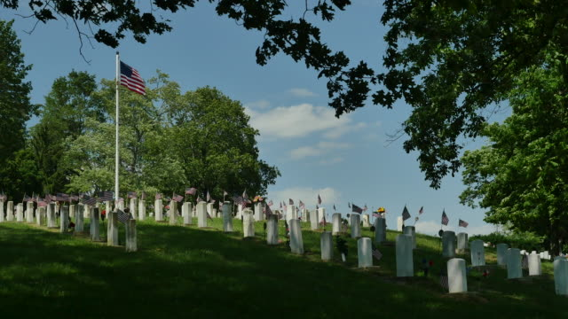 national veterans cemetery with blowing flag zoom in 4k - memorial stock videos & royalty-free footage
