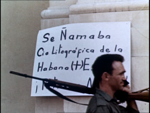 stockvideo's en b-roll-footage met nationalizing the industries of cuba / armed guards on patrol of the banks and businesses - bewaken