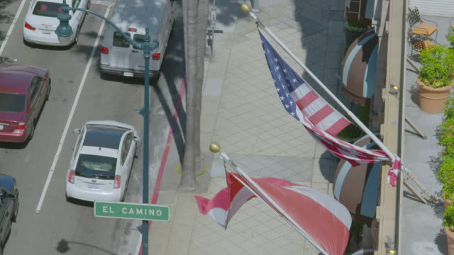 MS HA Nationals flags waving on top of Beverly Wilshire Hotel, cars moving on street / Beverly Hills, Los Angeles County, California, United States