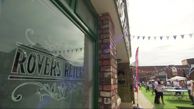 nationwide sports day called 'i am team gb' held manchester ext low angle view cobbles on coronation street set 'rovers return' window with people... - コロネーションストリート点の映像素材/bロール