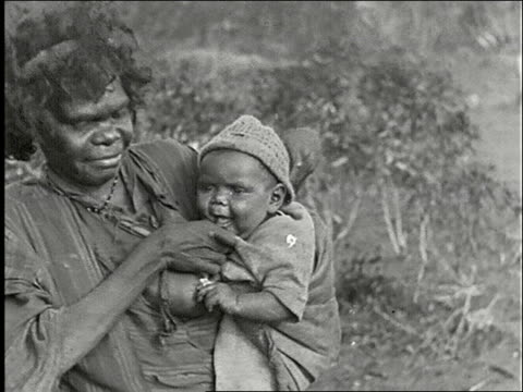 native aborigine family in bush cooking over a fire / woman nurses young baby two men and one woman seated on ground with body paint use axe and... - boomerang stock videos & royalty-free footage