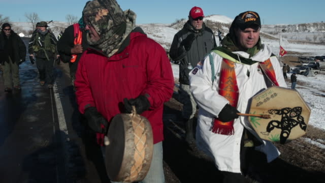 Native American activists march following an interfaith ceremony at Oceti Sakowin Camp on the edge of the Standing Rock Sioux Reservation on December...