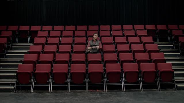 native american college student sitting down in empty auditorium - zuschauerraum stock-videos und b-roll-filmmaterial