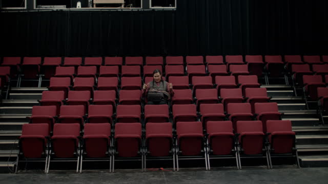 Native American college student sitting down in empty auditorium