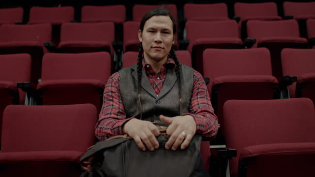 vidéos et rushes de native american college student sitting in auditorium, looking into camera - auditorium