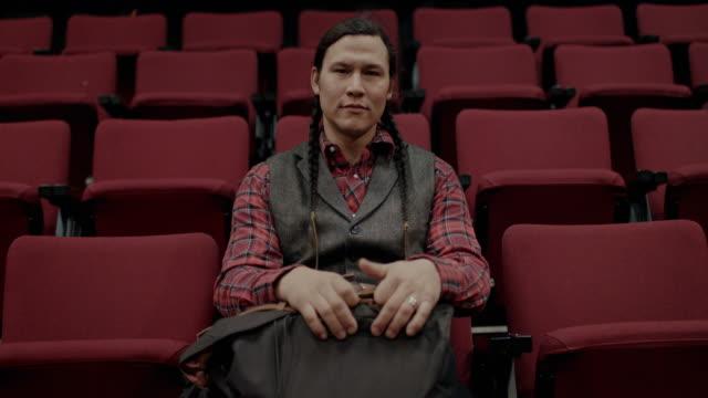 native american college student sitting in auditorium, looking into camera - zuschauerraum stock-videos und b-roll-filmmaterial