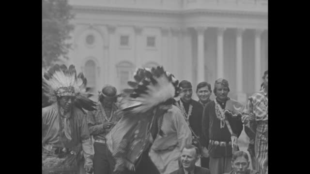 vídeos de stock e filmes b-roll de native american drummer in the midst of other native americans and lawmakers rep will rogers at left and sen elmer thomas at right seated crosslegged... - anasazi