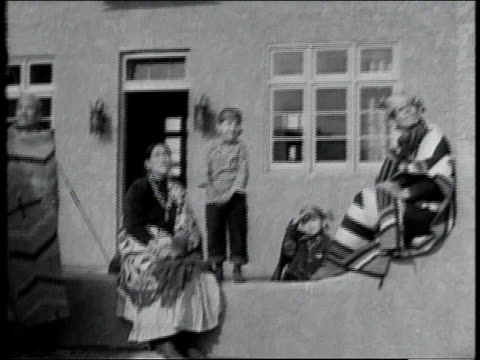 vídeos de stock e filmes b-roll de 1928 montage native american family sitting outside home watching plane taking off / united states - 1928