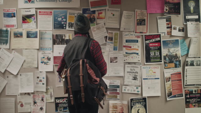 native american graduate student looking at notice board - classified ad stock videos and b-roll footage