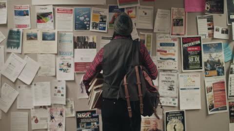 vídeos y material grabado en eventos de stock de native american graduate student looking at notice board - universidad