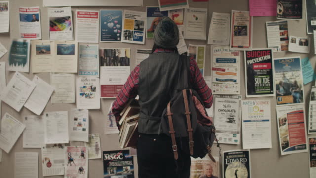vídeos de stock, filmes e b-roll de native american graduate student looking at notice board - classified ad