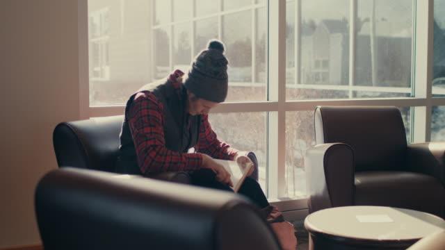 vídeos y material grabado en eventos de stock de native american graduate student sitting by the window, reading - un solo hombre