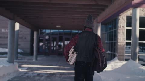 vidéos et rushes de native american graduate student walking into college building - motivation