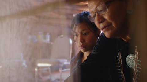 vídeos de stock, filmes e b-roll de uma avó nativa americana (navajo) em seus sessenta anos ensina sua neta adolescente como tecer em um tear dentro de casa - tribo norte americana