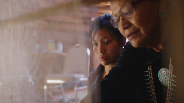 a native american grandmother (navajo) in her sixties teaches her teenaged granddaughter how to weave at a loom indoors - native american reservation stock videos & royalty-free footage