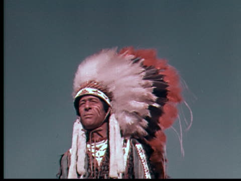 1955 montage ms cu native american indian chief wearing full headdress / usa - ネイティブアメリカン点の映像素材/bロール