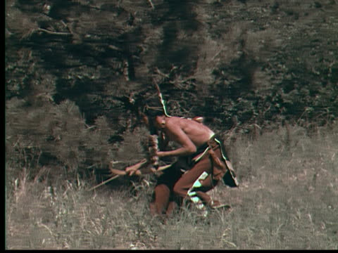 vídeos de stock e filmes b-roll de 1955 ws pan native american man hunting with bow and arrow / usa - cultura tribal da américa do norte