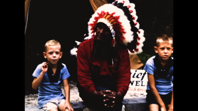 native american man in headdress made of feathers sitting in front of tent and two white boys dressed in blue partial sign behind them with the words... - headdress stock videos & royalty-free footage