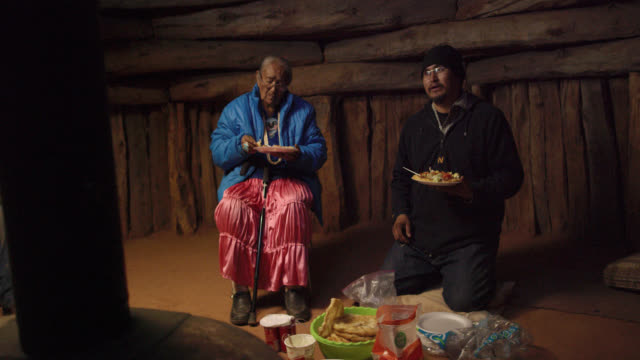 a native american man (navajo) in his forties kneels on the floor of a hogan (navajo hut) eating food and talking with others as he sits next to an elderly woman also eating - erzählen stock-videos und b-roll-filmmaterial