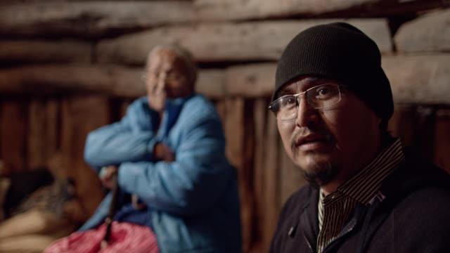 un uomo nativo americano (navajo) in his forties parla in primo piano mentre una donna anziana sui sessant'anni ascolta in background - minoranza video stock e b–roll