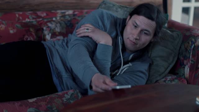 native american man sleeping on sofa, checking time on phone - alarm clock stock videos & royalty-free footage