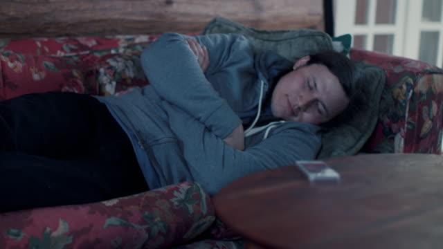 vídeos de stock e filmes b-roll de native american man sleeping on sofa, checking time on phone - napping