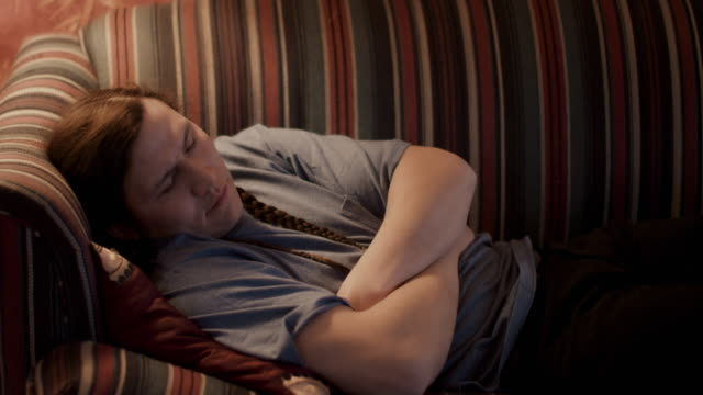 native american man sleeping on sofa - napping stock-videos und b-roll-filmmaterial