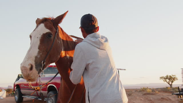 native american navajo teenage boy prepping and mounting his horse in monument valley arizona or utah at dusk - one teenage boy only stock videos & royalty-free footage