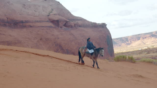 a native american, navajo teenage girl riding her horse up a steep sand dune near her home in the monument valley tribal park - recreational horse riding stock videos & royalty-free footage