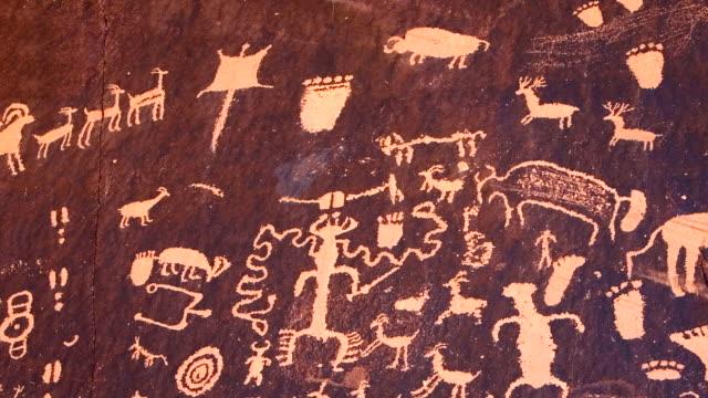 vidéos et rushes de cu pan native american petroglyphs on sandstone rock near monticello, newspaper rock / utah, united states  - utah