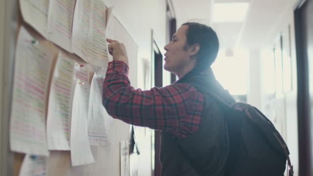 native american student looking at notice board - vetrinetta video stock e b–roll