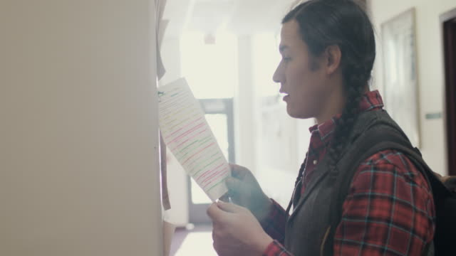 native american student looking at notice board - school bulletin board stock videos and b-roll footage