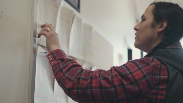 native american student looking at notice board - motivation stock-videos und b-roll-filmmaterial
