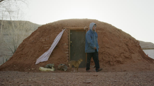 a native american (navajo) teenaged boy opens the door and exits a mud hogan (navajo hut) and is met by his pet dog - one teenage boy only stock videos & royalty-free footage