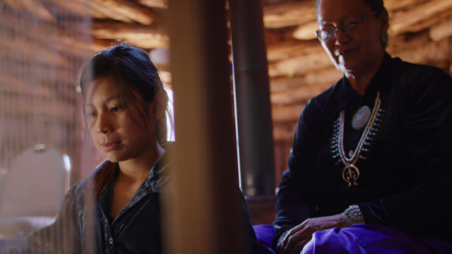 a native american teenaged girl weaves at a loom while her grandmother in her sixties oversees indoors in a hogan (navajo hut) - navajo culture stock videos & royalty-free footage