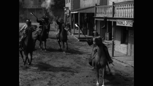 vídeos y material grabado en eventos de stock de native american warriors firing weapons and carrying torches while riding on horses into town - western usa