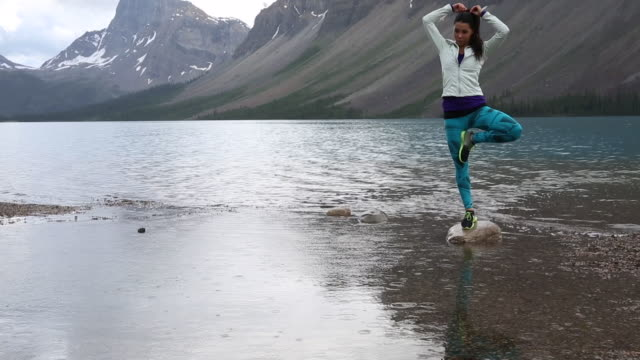 Native American woman assumes yoga stance at edge of mountain lake
