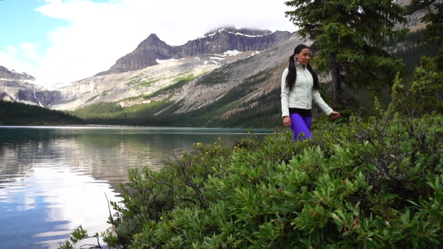 native american woman follows trail, looks out across mountains and lake - haarzopf stock-videos und b-roll-filmmaterial