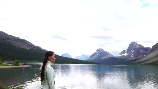 Native American woman follows trail, looks out across mountains and lake