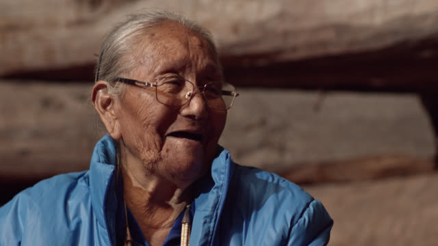 a native american (navajo) woman in her eighties talks to and laughs with a man in his forties while they eat - north american tribal culture stock videos & royalty-free footage