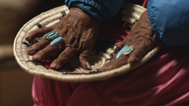 vídeos de stock e filmes b-roll de a native american woman (navajo) in her eighties wearing turquoise rings on her fingers touches and looks at a woven navajo basket - cultura tribal da américa do norte