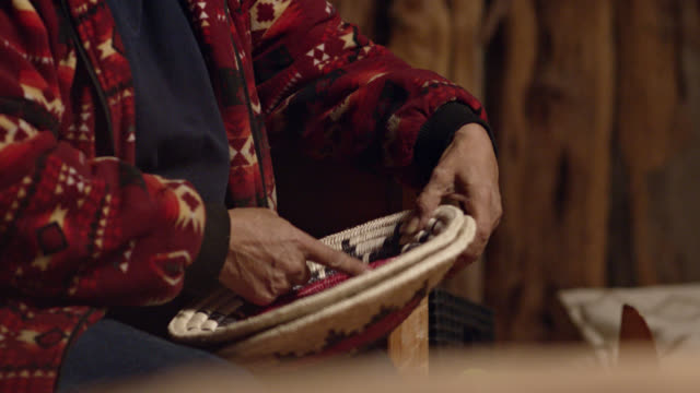 a native american woman (navajo) in her sixties discusses a woven navajo basket while pointing at it indoors - minority groups stock videos & royalty-free footage